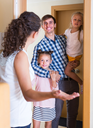 guests: Young woman welcoming smiling awaited guests at the doorway Stock Photo