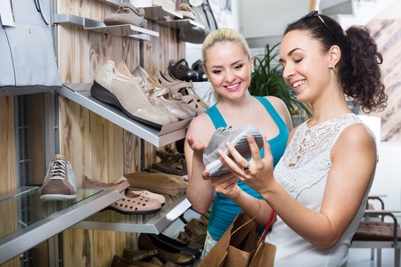 Ttwo glad young women selecting a shoes and chatting among shelves. Focus on right person
