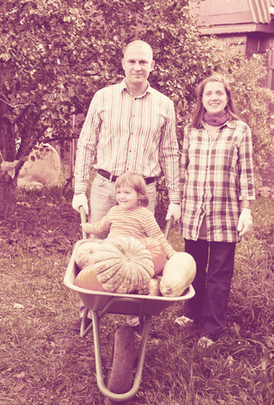 Happy  family with harvested pumpkins in garden Stock Photo