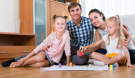 Cheerful young parents and two little daughters with board game at home