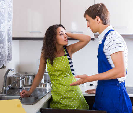 bribes: Unprofessional adult spanish plumber asking furious young woman for bribes indoors Stock Photo