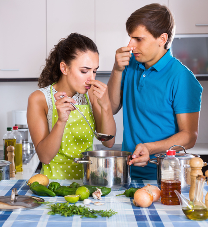stinking: Unhappy couple with stinking veggies food in domestic kitchen