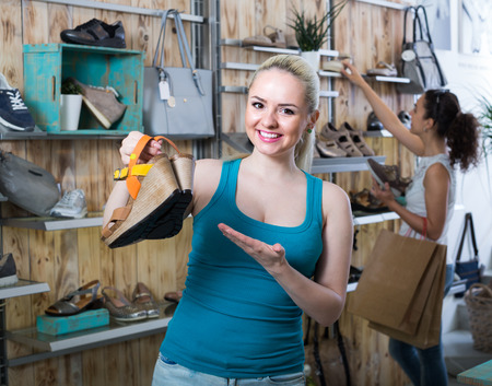 desires 25: ?Young cheerful girl showing a chosen pair of shoes while her friend still choosing in store Stock Photo