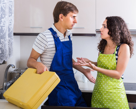 bribes: Unprofessional plumber asking furious young unhappy european woman for bribes indoors Stock Photo