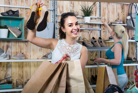desires 25: happy girl holding a picked pair of shoes in the boutique