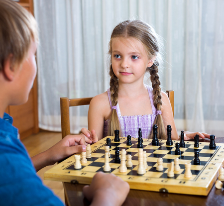 Cheerful boy and little girl playing chess at home Stock Photo