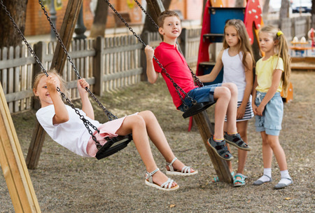 frisky: View on  cheerful frisky children swinging together on childrens playground in town