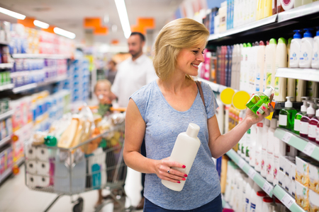 haircare: Smiling female customer selecting haircare products in supermarket
