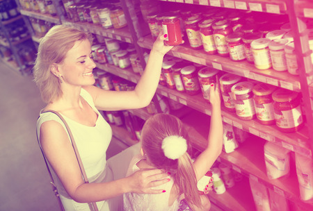 a jar stand: joyful woman with little daughter choosing preserve tomato sauce in jar in food shop