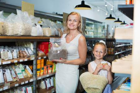gladly: Portrait of positive young woman and cheerful girl gladly shopping groats in supermarket