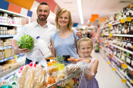 Portrait of smiling family standing with full cart in supermarket Stock Photo