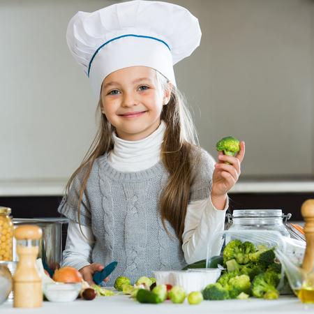 Portrait of cute little girl in cook cap cooking veggies Stock Photo