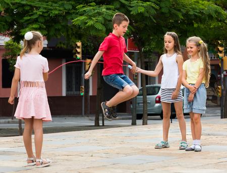groep lachende kinderen springen samen met springtouw op stedelijke speelplaats Stockfoto
