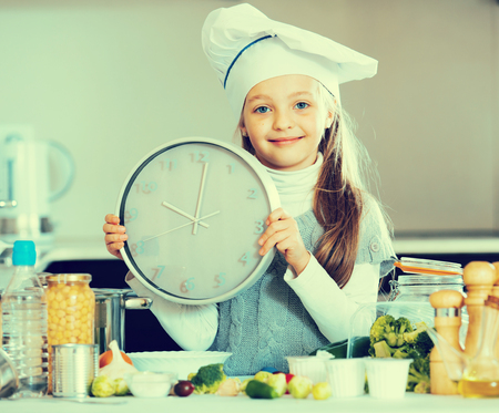 Girl with ponytails holding clock at kitchen table and smiling Stock Photo