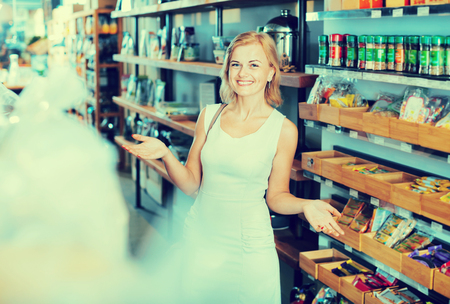 Smiling happy positive young woman standing among shelves in grocery store