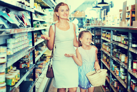gladly: Portrait of happy young woman and cute cheerful girl gladly shopping in supermarket