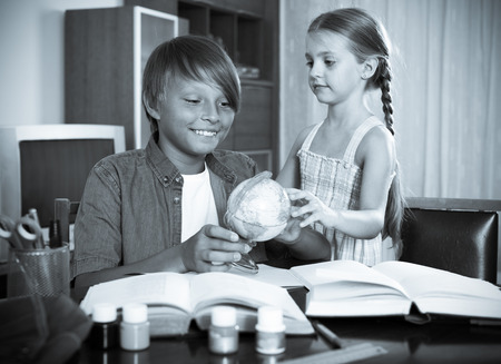 big brother: Happy big brother helping little girl to do homework at home. Focus on the boy