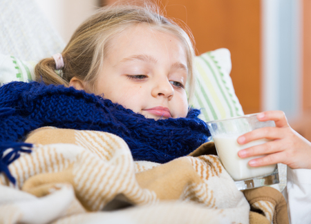 Little girl under blanket with warm milk and fever indoors Stock Photo