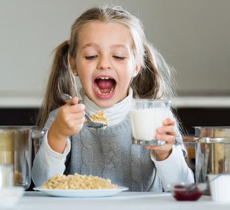 kasha: Small girl having breakfast with oatmeal porridge indoors