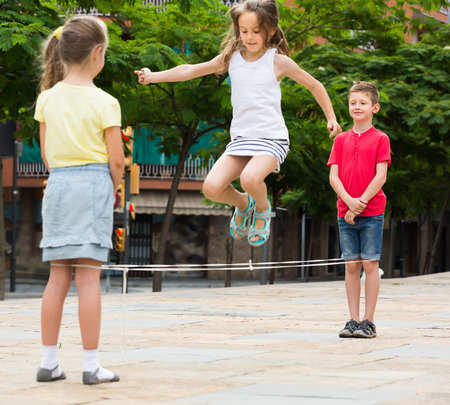 Smiling kids in school age playing together with chinese jumping rope outdoors. Focus on boy