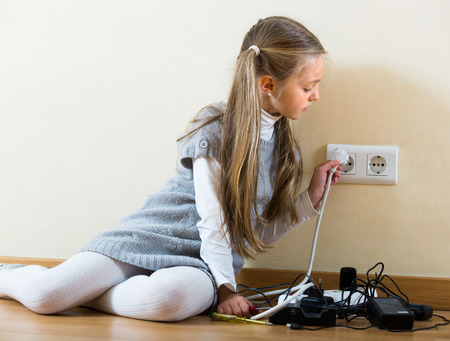 absent: Little girl dangerously playing with sockets and electricity while her parents absent