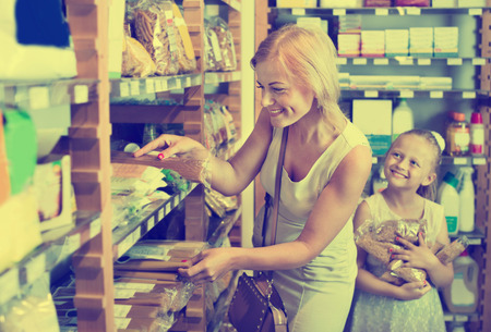 gladly: Portrait of  young woman and  cute cheerful girl gladly shopping different kinds of pasta in supermarket