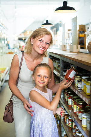 crushed cans: smiling female customer with little daughter choosing preserve tomato sauce in jar in food shop Stock Photo