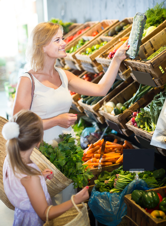 gladly: Portrait of happy woman and kid gladly shopping in supermarket