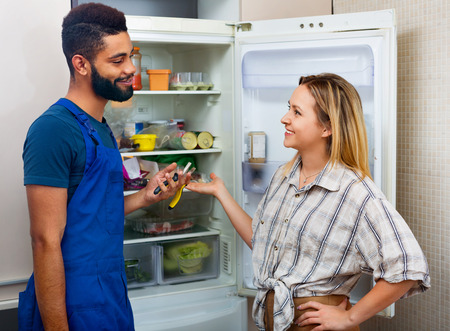 complaining: White smiling woman complaining to black handyman on problems with fridge Stock Photo