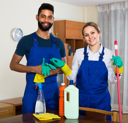 office cleanup: Portrait of smiling black and white professional cleaners in overalls working indoors Stock Photo