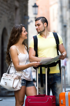 Smiling couple with map chasing city streets and looking for hotel
