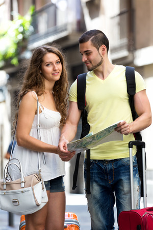 routing: Happy guy and long-haired girl with map chasing city streets and looking for hotel