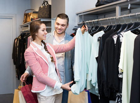 gladful: Happy smiling young couple choosing new apparel in store. Focus on girl Stock Photo