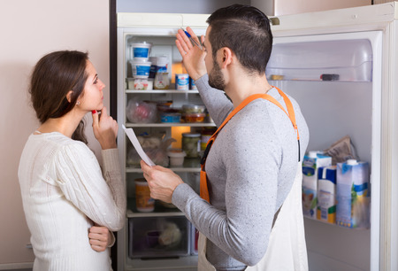 aftersales: Professional workman visiting housewife customer for after-sales service of refrigerator