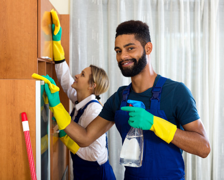 dusting: Cheerful cleaners cleaning and dusting in ordinary house