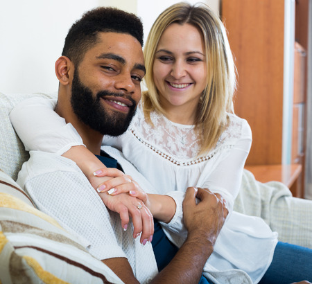 limp: Happy spouses sitting on sofa, hugging and smiling indoors Stock Photo