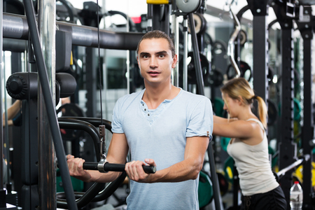 under control: Positive active people having strength training under coach control in gym