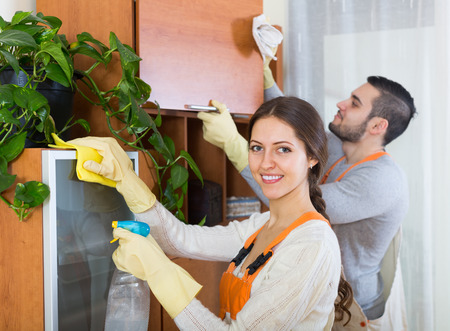houseman: Professional cleaners team in uniform working at clients home. Focus on girl