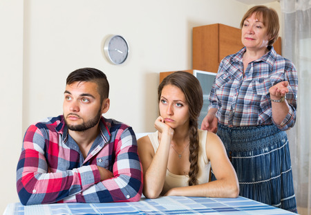 Home conflict between displeased young couple and elderly female. Selective focus Stock Photo