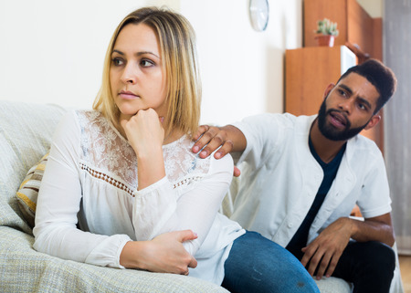 interracial family: Young interracial family couple with serious faces arguing at home Stock Photo