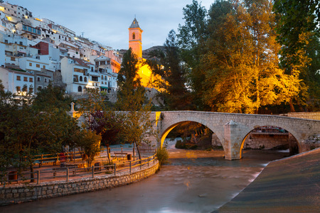 dusk view of Alcala del Jucar with river and bridge. Province of Albacete, Spain Stock Photo