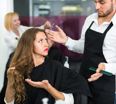 25s: Displeased young attractive girl has a serious conversation with the hairdresser