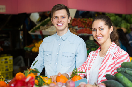 happines: Smiling husband and young brunette wife choosing veggies and fruits . Focus on man Stock Photo