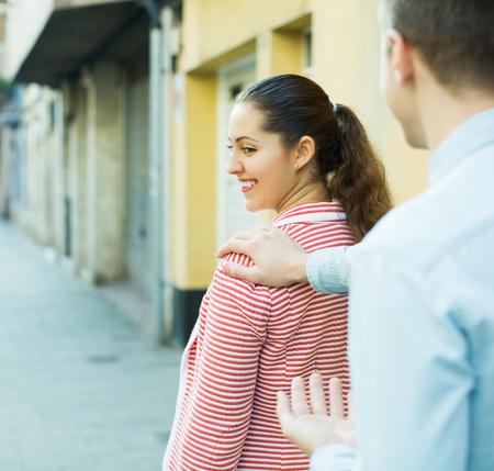 sidewalk talk: Brunette girl flirting with hadsome guy at the street