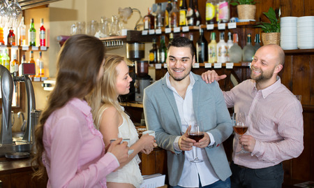 acquaintance: Casual acquaintance of cheerful smiling young adults at bar. Selective focus Stock Photo