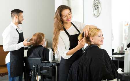 haircutter: Hair stylist working on haircut for smiling girl