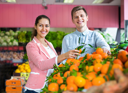 happines: Young brunette girl and smiling boyfriend buying citruses in grocery store Stock Photo