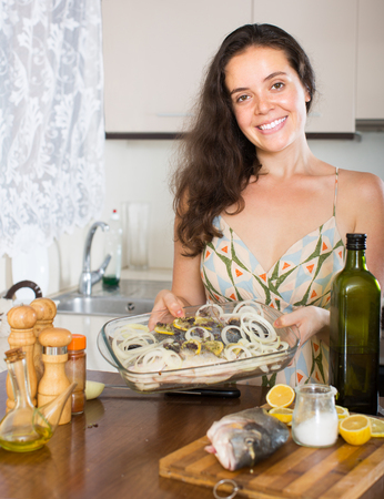 fryingpan: Young smiling housewife putting pieces of lemon in fish at home kitchen Stock Photo
