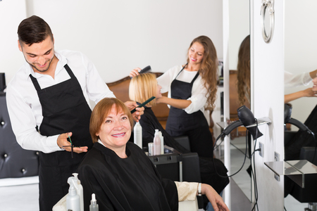esthetics: Mature person doing haircut at the hair salon with hairdresser and smiling Stock Photo