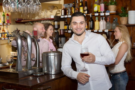 entertaining: Positive bartender entertaining guests at the bar counter